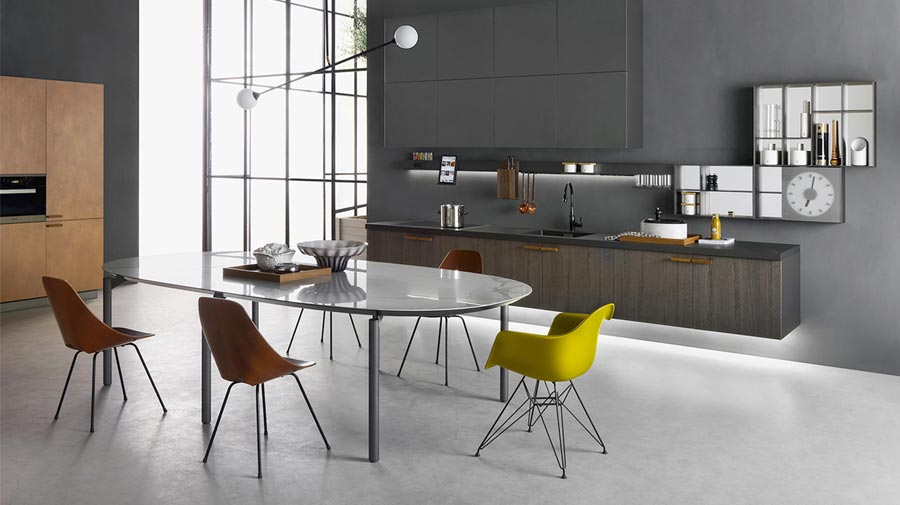 A modern kitchen with sombre colours and wall-mounted furniture