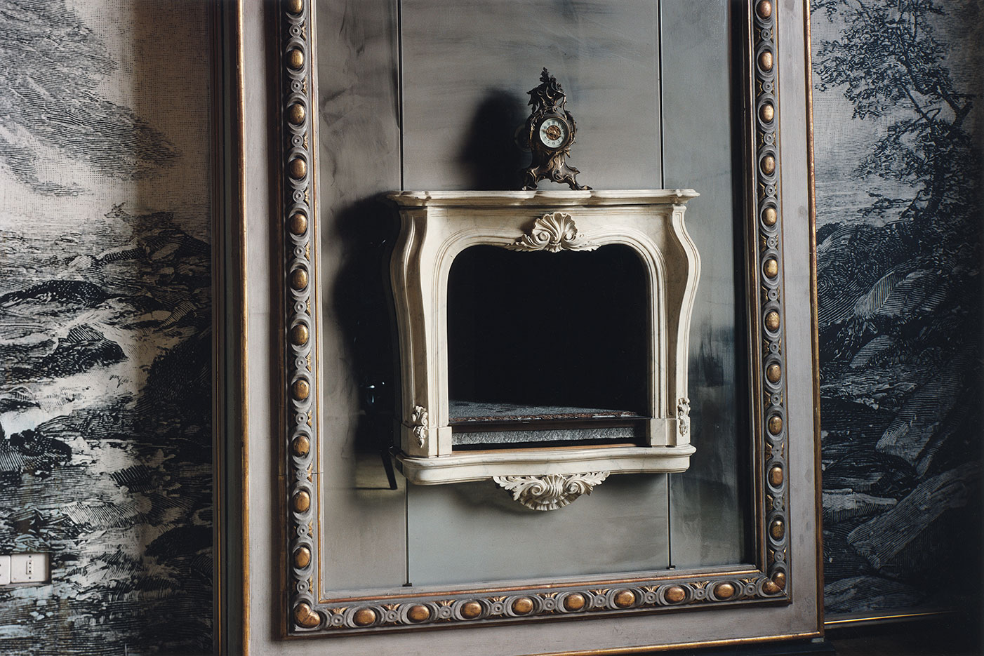 The fireplace. Designed by Mollino himself, framed by a mirror which has become matte over time. On the background wall, the pictures of a peaceful nature create the illusion of a limitless room......