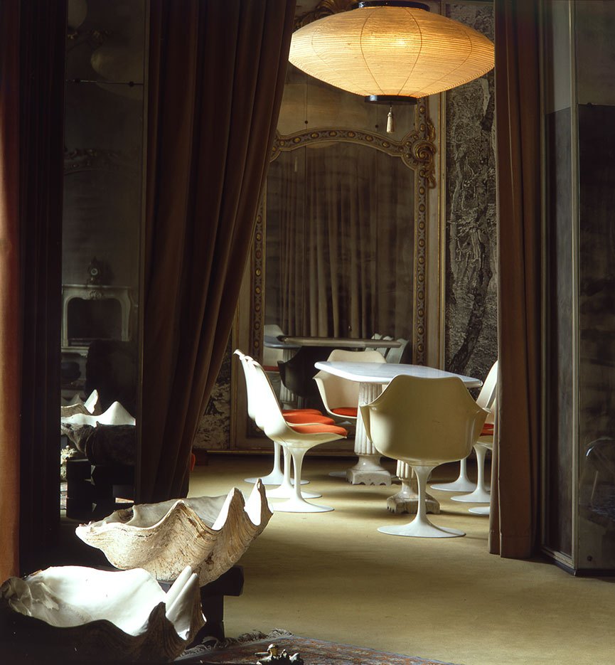 Tulip chairs by Saarinen alongside large shells and an oriental lamp in rice paper. The curtains are throughout the flat and modify the spaces.