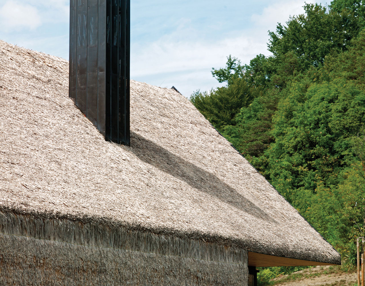 A detail of the thatched roof and the connection to the vertical wall.