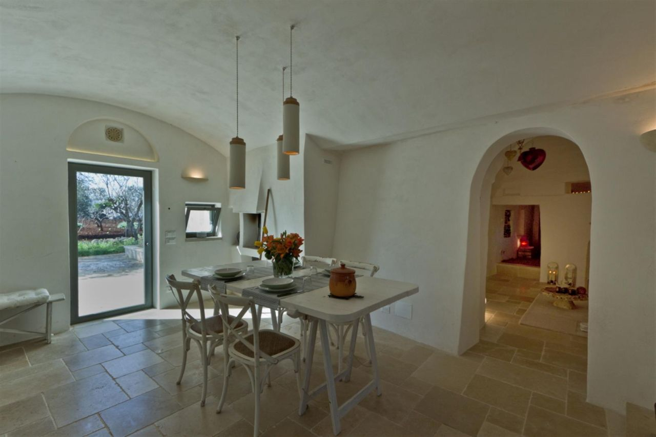 Designer lamps modernize a pure-white interior. Flooring in local limestone