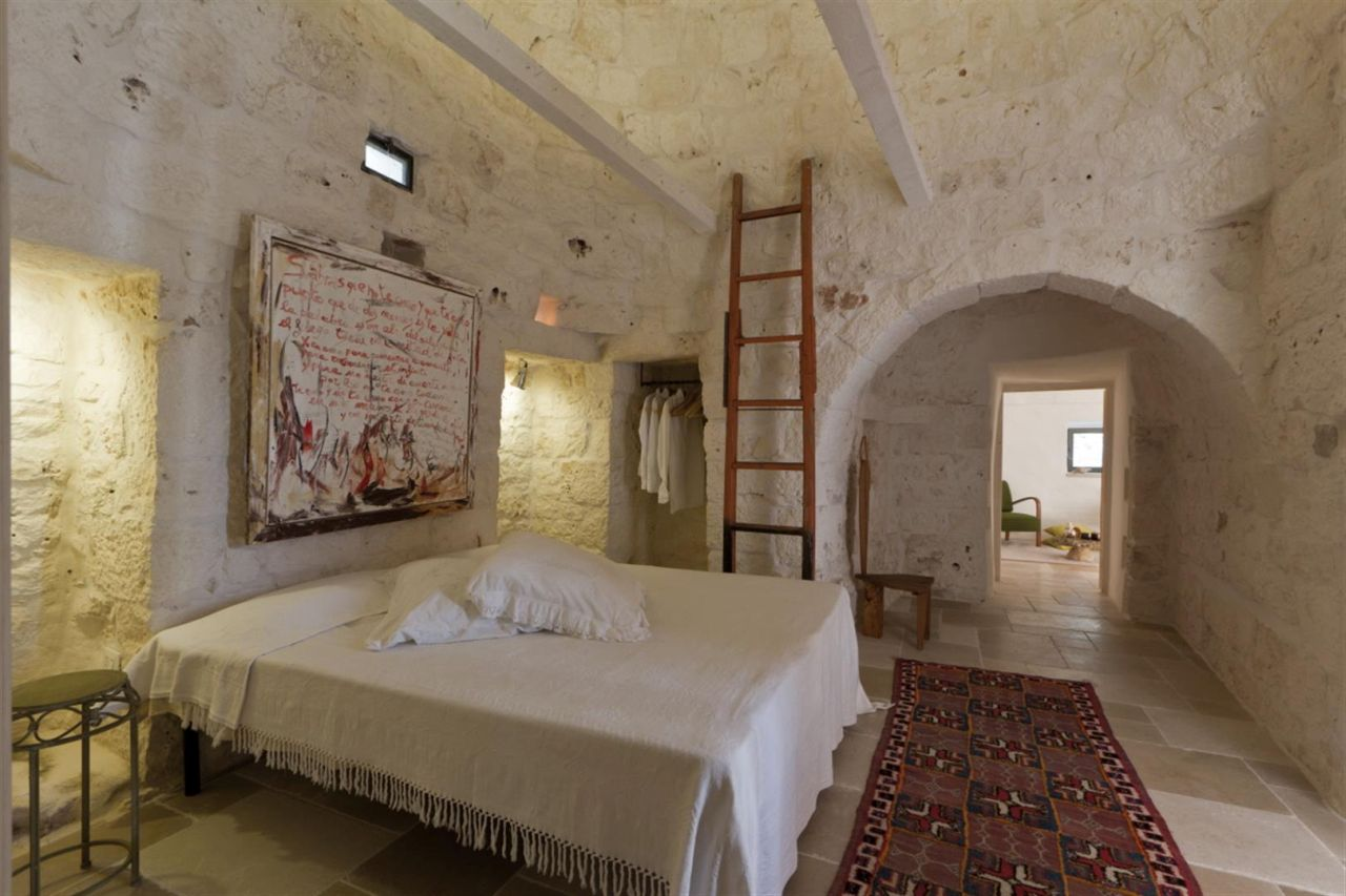 In the largest trullo, the master bedroom with its own outside glass door.