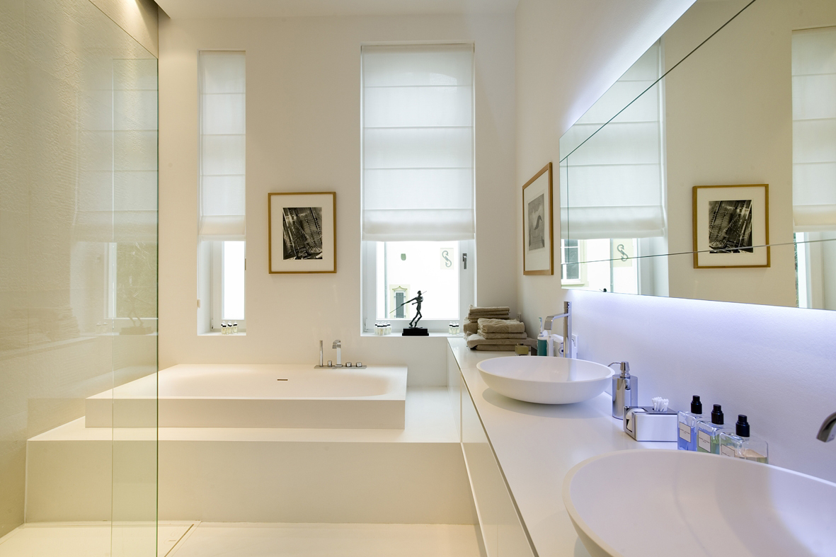 Above the washbasins, a large mirror creates a bigger space in the bathroom