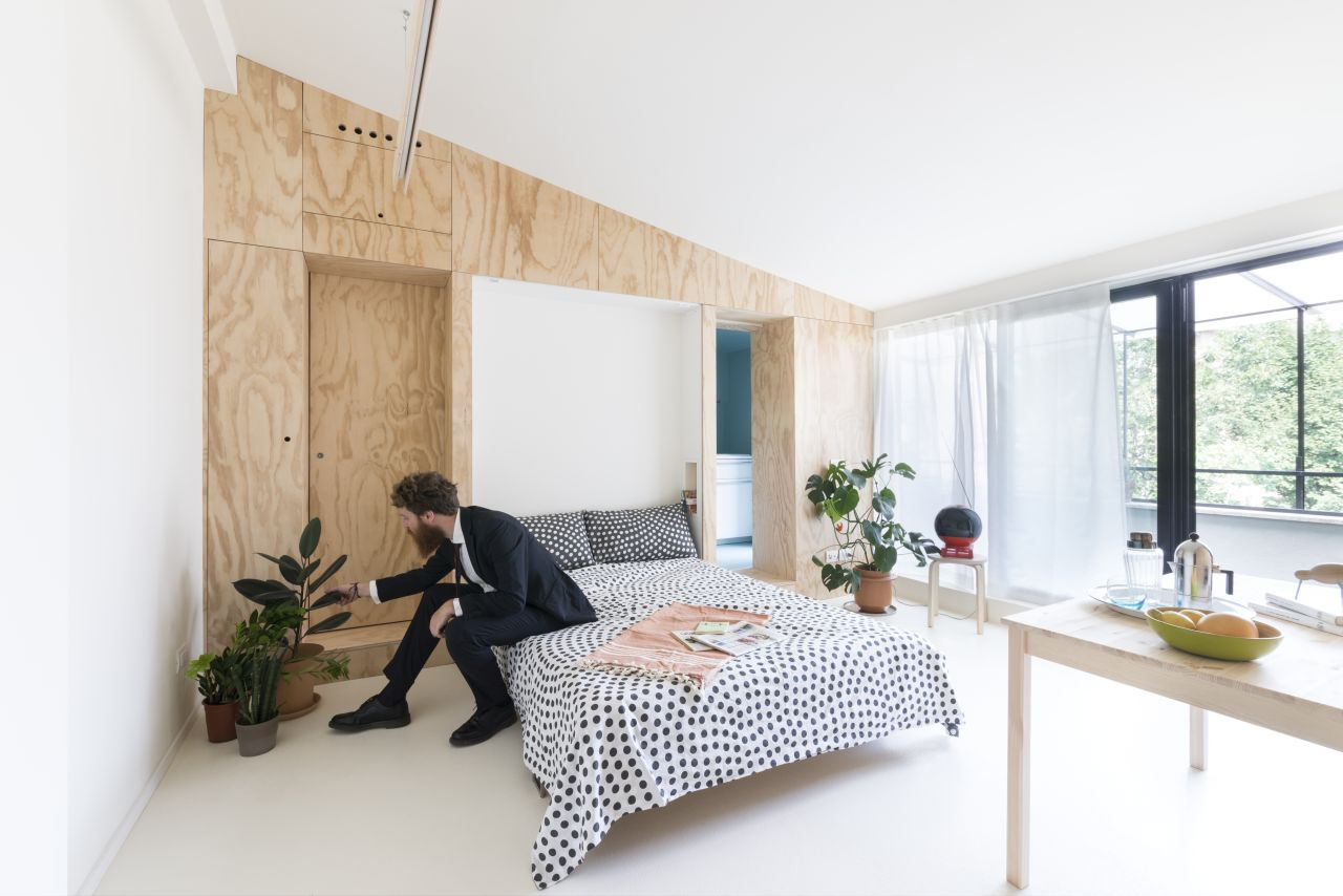 the studio apartment in the morning with the foldable double bed and the table
