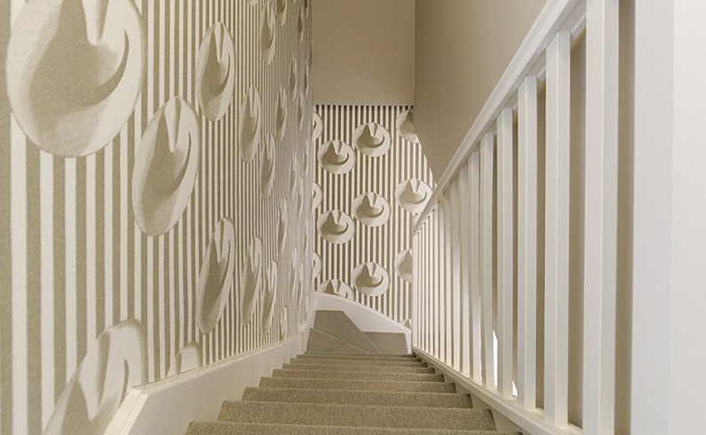 Bannister and wall mimic the patterned wallpaper by Elitis.