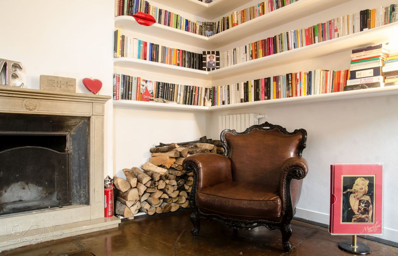 A reading corner in the living room, with stone fireplace and period armchair in leather.