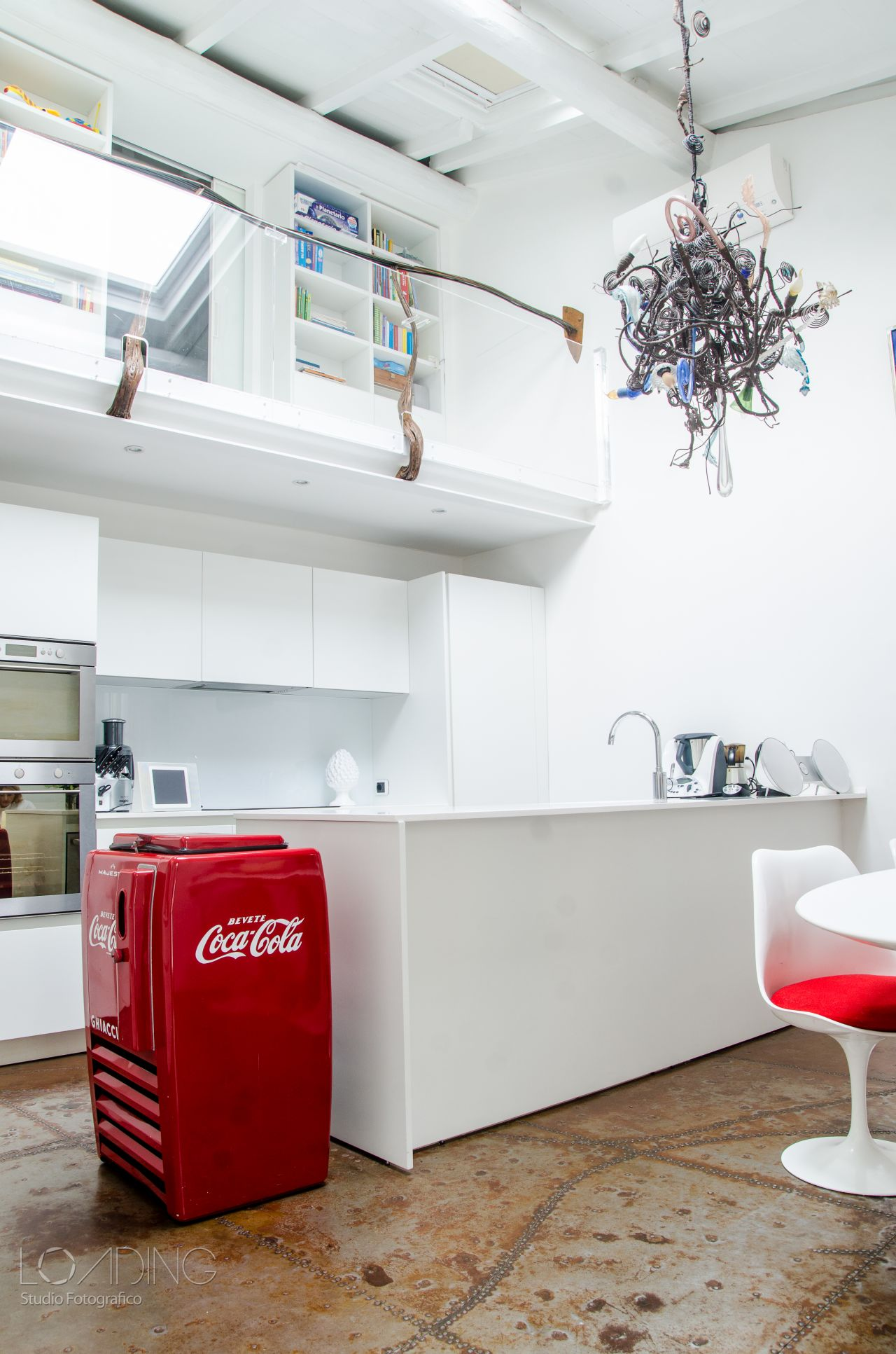 The white kitchen (Elmar) disappears almost entirely and next to it, splashes of colours on cushions and the fifties' vintage fridge.