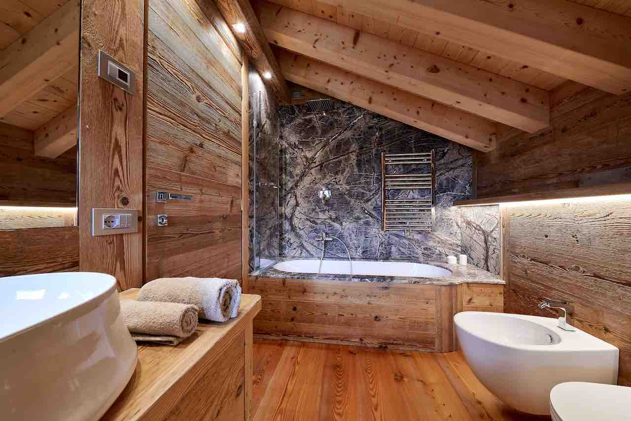 In the bathroom, made entirely out of wood, centre stage is occupied by the tiny bathtub with its spectacular cladding in forest Green marble