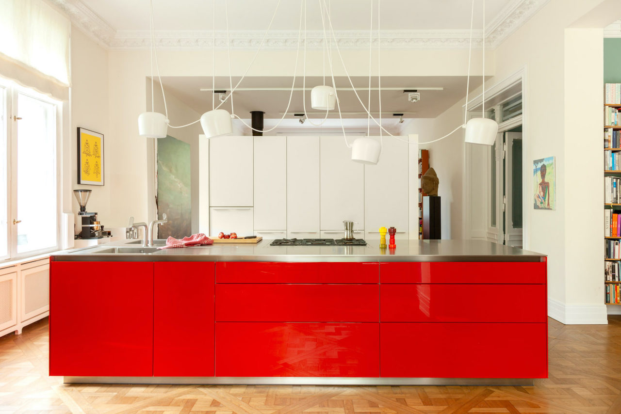The bright red island separates the kitchen from the rest of the open living room.