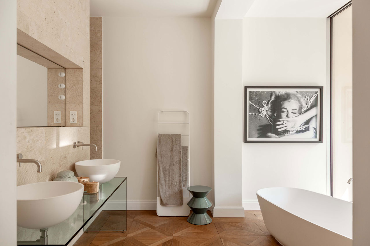 Light-colored walls and washbasins with a transparent glass countertop.