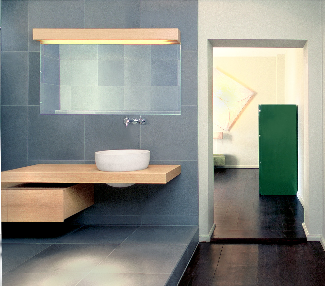 In the bathroom: tiles in natural stone and functional timber furniture.