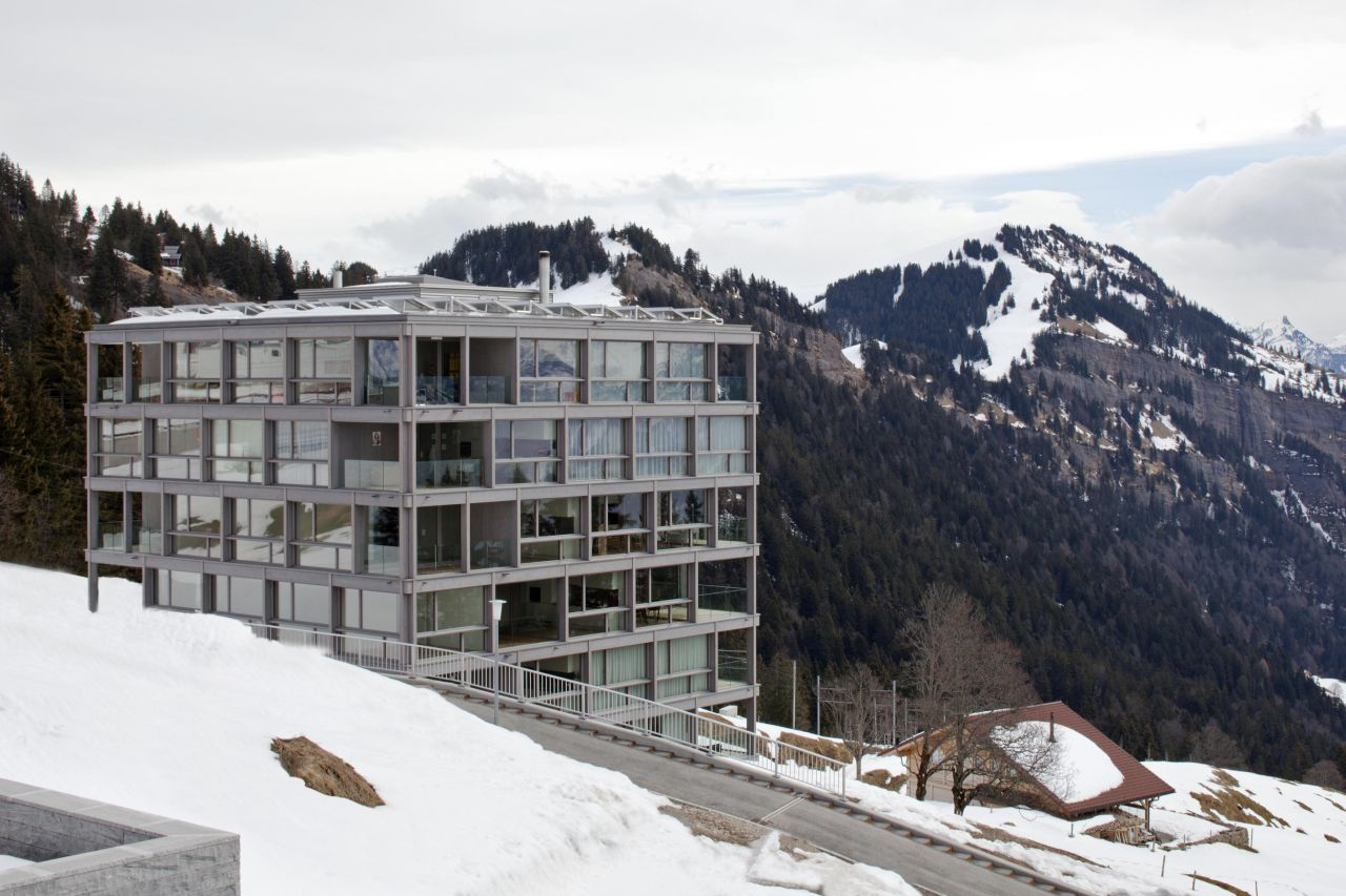 A load-bearing frame in reinforced concrete. A clean-cut cube, sincere in its modernity. This building wants to blend with the mountain stone, it mirrors the surrounding landscape and is not at...