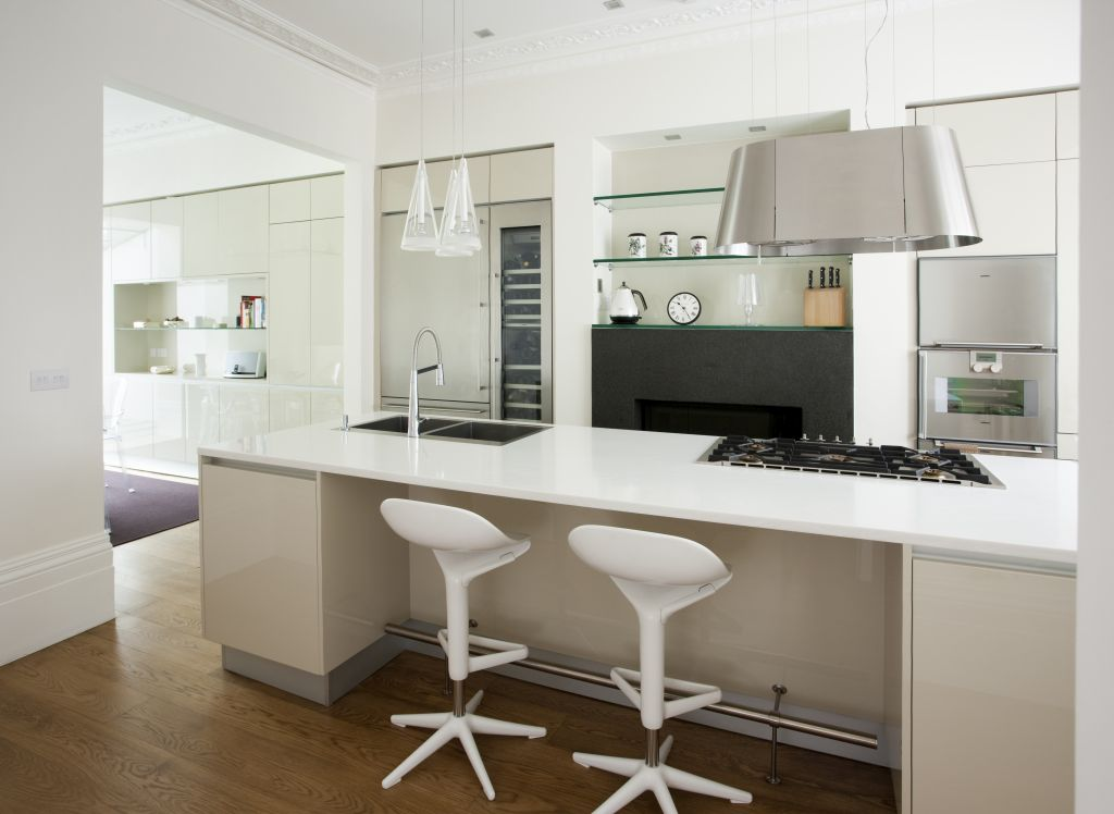 Kitchen island by Pedini, an electric hob designed like a chandelier, in background, behind the Twin hob by Elica, a fridge by Gaggenau.
