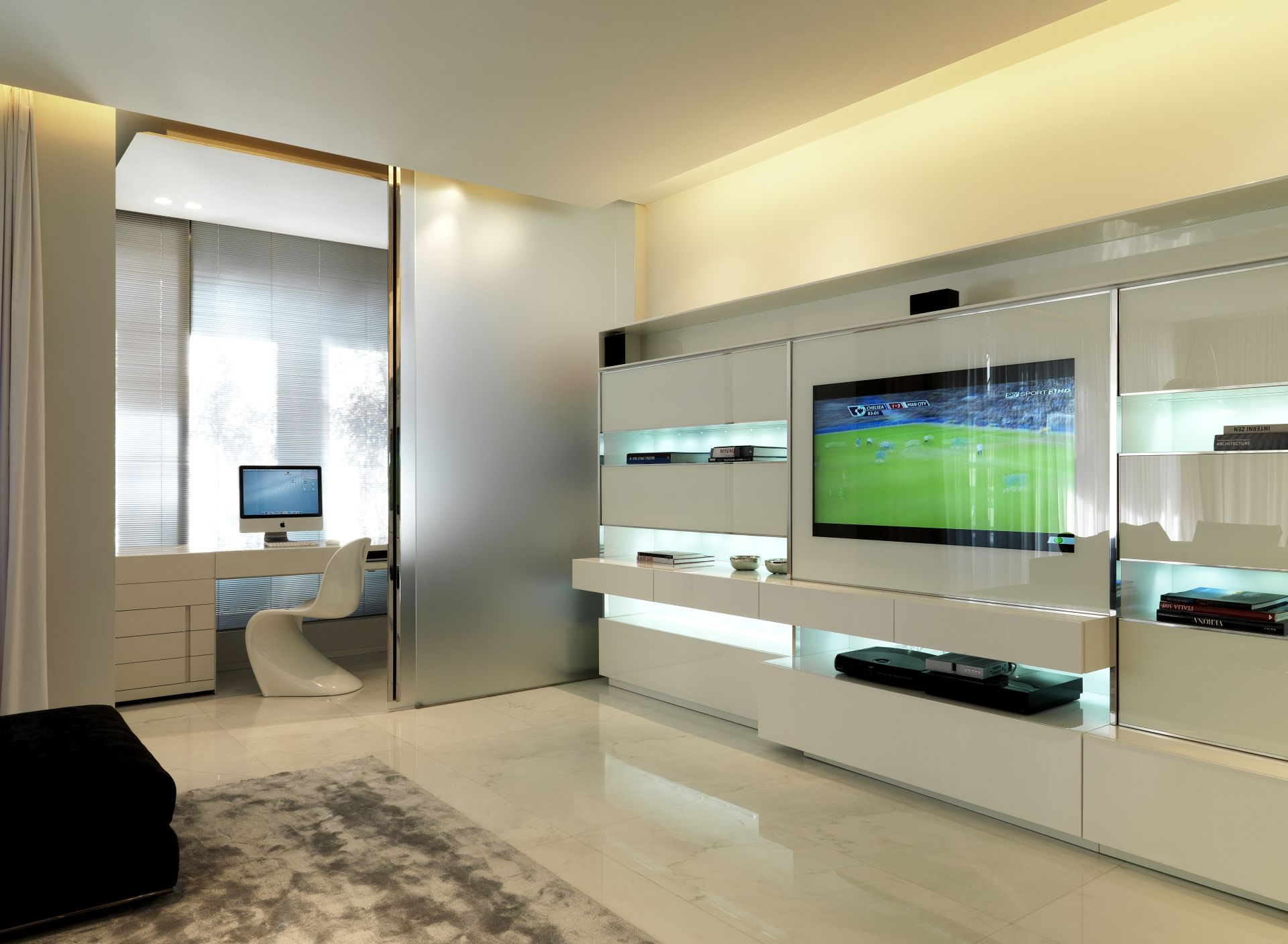 The large flat screen TV shows a football match. Here, watching a game is a favourite past-time.
