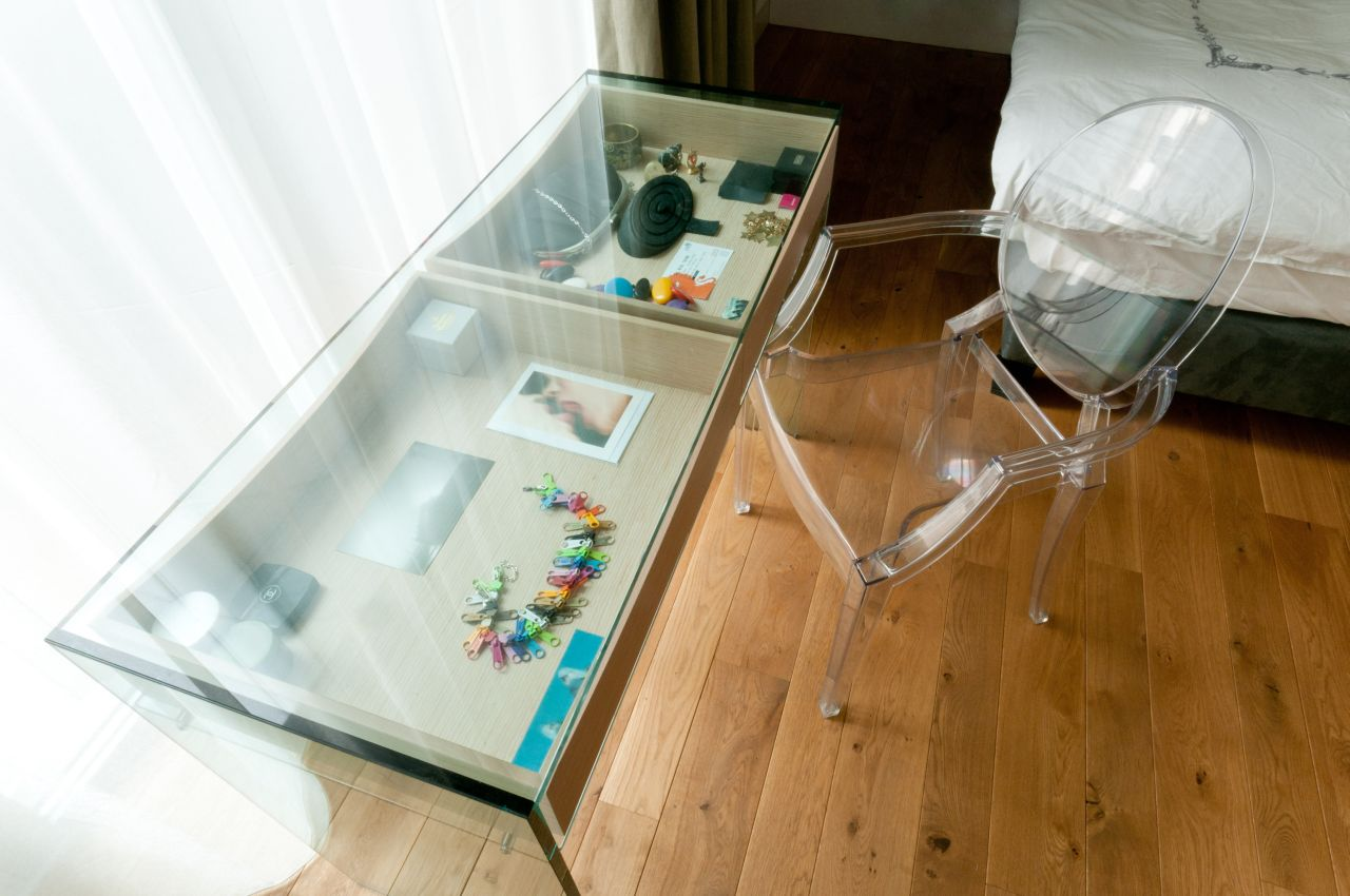 A console table with a glass top, to display small objects. To the right, Ghost chair by Philippe Starck for Kartell.