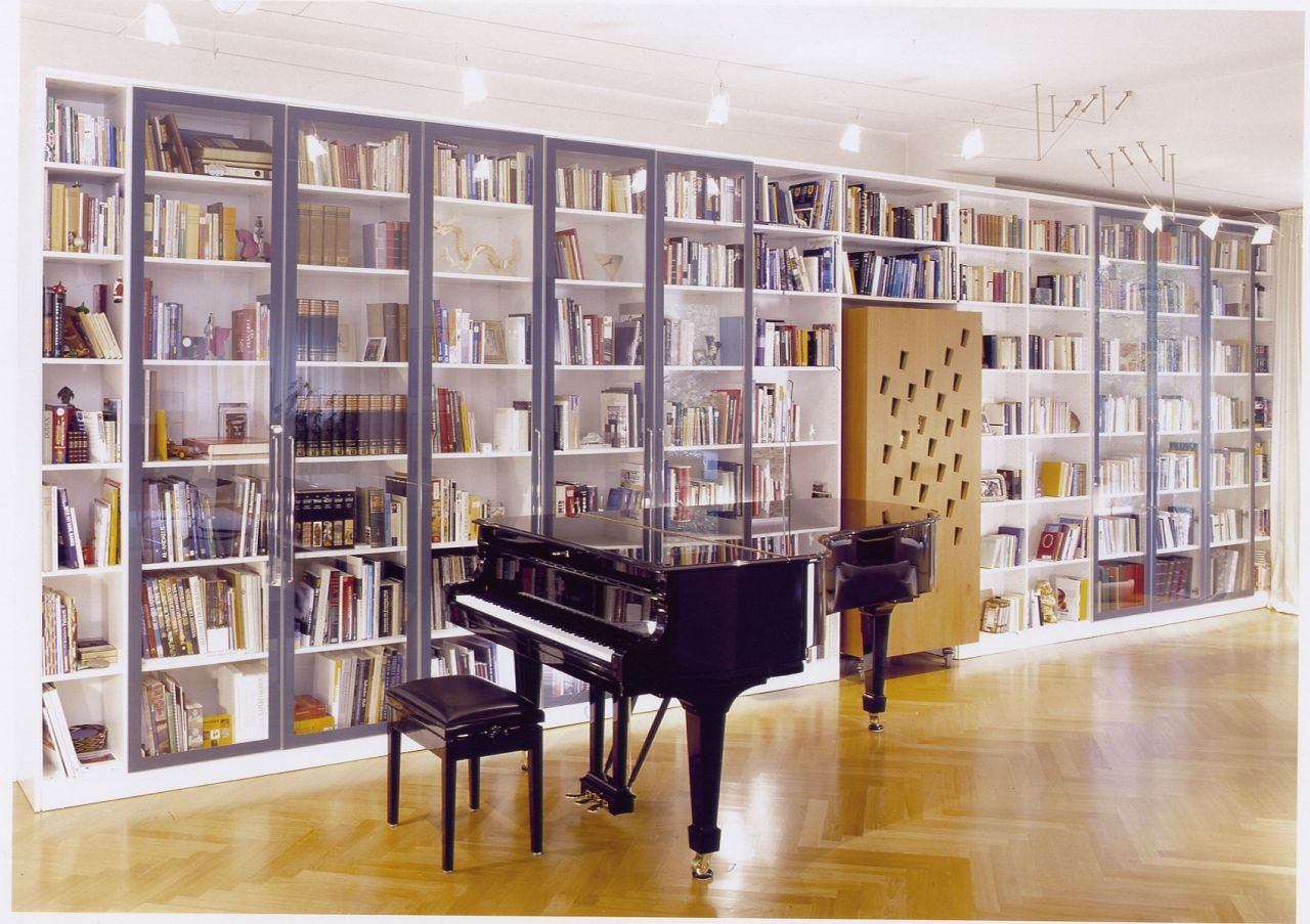 In the music room, a grand piano and a large bookcase