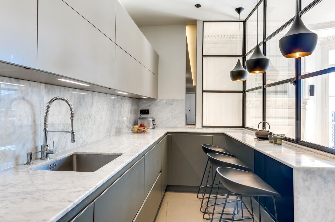 Minimalist kitchen with counter top in Carrara marble and stools by Hay