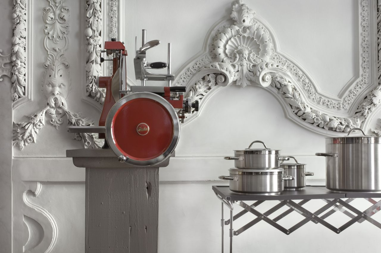 Kitchen corner. To the left, a flywheel slicer by Berkel and to the right, pots by Paderno displayed on a trolley by Kartell.